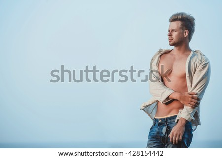 Handsome man model posing on the sea beach. man beach, man ocean, man model sea, man travel, guy model chest, man model beach posing, man model sexy, man water, man sand, handsome man, Muscle man - stock photo