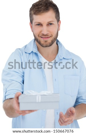 Handsome man offering a present looking at camera on white background