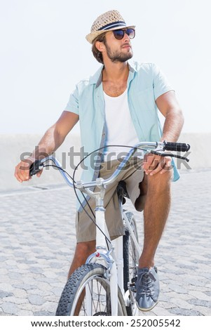 Handsome man on a bike ride on the pier on a sunny day - stock photo