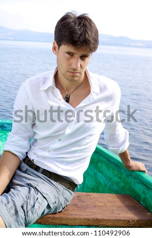 Handsome man on a boat in a lake posing serious vertical - stock photo