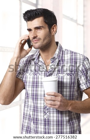 Handsome man on phone holding morning coffee. - stock photo