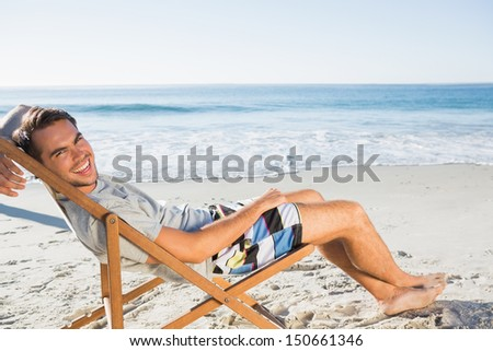 Handsome man on the beach lying on his deck chair smiling at camera