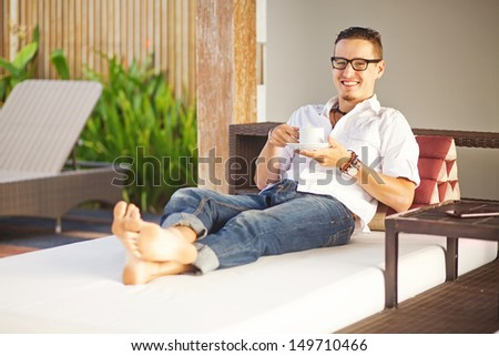 Handsome man on the outdoor bed in the garden of house - stock photo