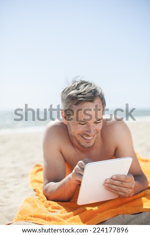 handsome man on the seaside lying on a beach towel to use a digital tablet - stock photo
