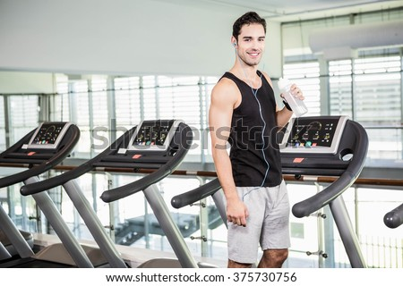 handsome man on treadmill drinking water at the gym - stock photo
