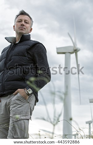 Handsome man. Outdoor male portrait over landscape with wind turbines. Image toned. - stock photo