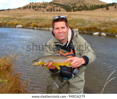 Handsome man outdoors in nature - holding a brown trout fish caught fly fishing in a mountain stream 					 - stock photo