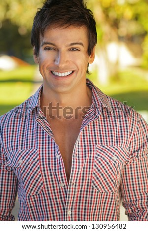 Handsome man outdoors with great big smile - stock photo