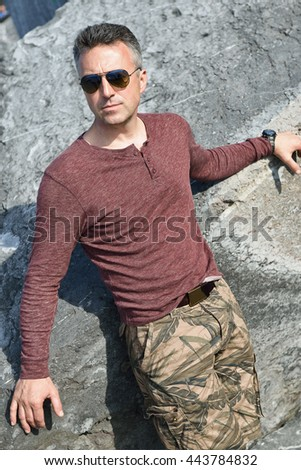 Handsome man over stone view. Outdoor male portrait.  - stock photo