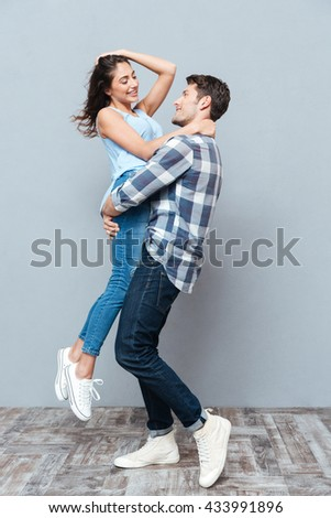 Handsome man picking up and hugging his girlfriend isolated on gray background - stock photo