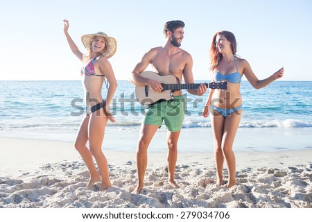 Handsome man playing guitar and his friends dancing at the beach