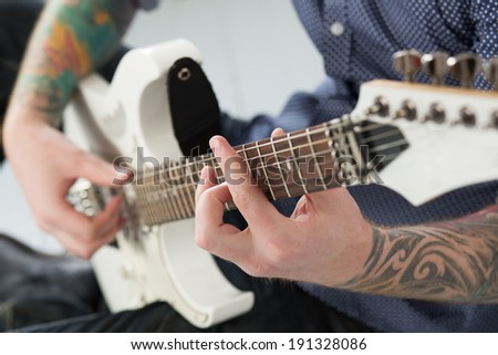 Handsome man playing on guitar - stock photo