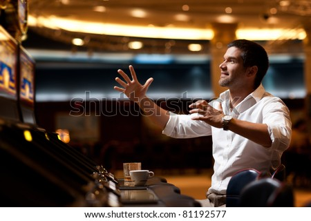 handsome man playing the slot machine, winning - stock photo