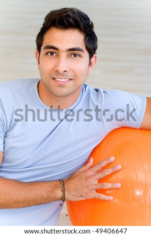handsome man portrait at the gym smiling leaning on a pilates ball - stock photo