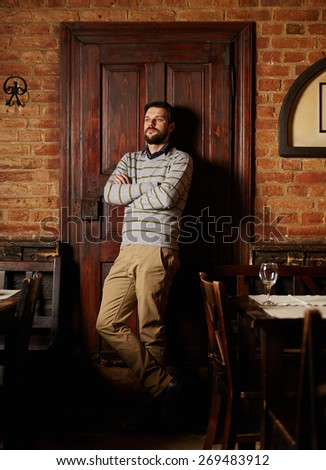 Handsome man posing in a vintage restaurant with arms folded - stock photo