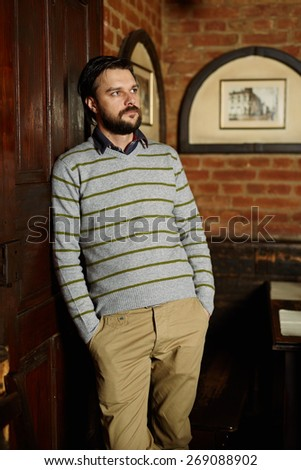Handsome man posing in a vintage restaurant with hands on pockets - stock photo