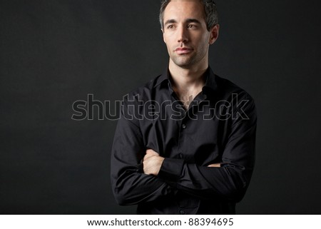 Handsome man posing in black shirt on dark background in studio. - stock photo