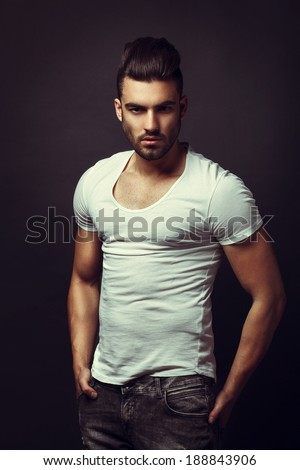 Handsome man posing in studio on dark background. Toned Image. - stock photo