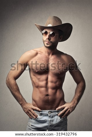 Handsome man posing with a cowboy hat - stock photo