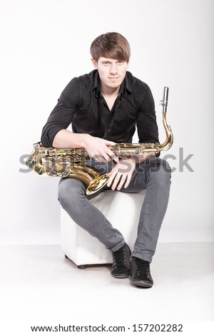 Handsome man posing with saxophone - stock photo