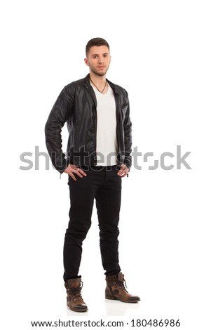 Handsome man posing. Young man in black leather jacket stands with hand on hip. Full length studio shot isolated on white. - stock photo