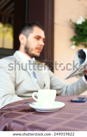 Handsome man reading a newspaper - stock photo