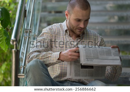 Handsome man reading a newspaper and thinking - stock photo