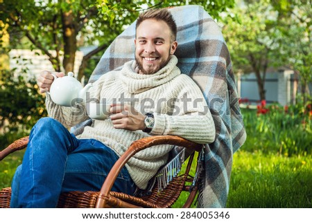 Handsome man relax in rocking-chair with teapot & cup in summer garden.  - stock photo