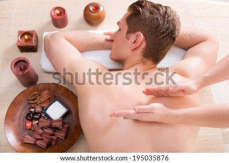 Handsome man relaxed and enjoying a deep tissue back massage at the spa salon. - stock photo