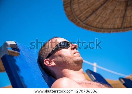 Handsome man relaxing on a sun bed