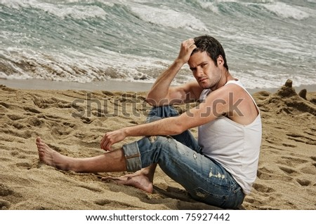 Handsome man relaxing on the beach - stock photo