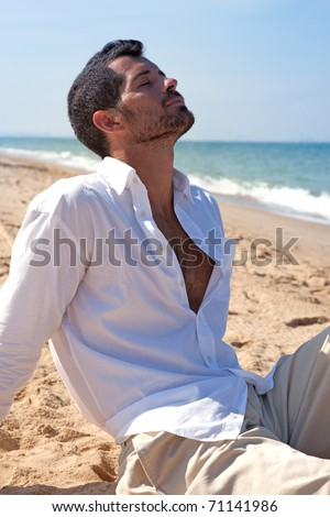 Handsome man relaxing on the beach, sitting on the sand wearing comfortable light clothes - stock photo
