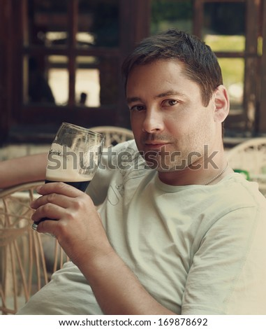 Handsome man relaxing with dark glass of beer in pub. Closeup portrait - stock photo