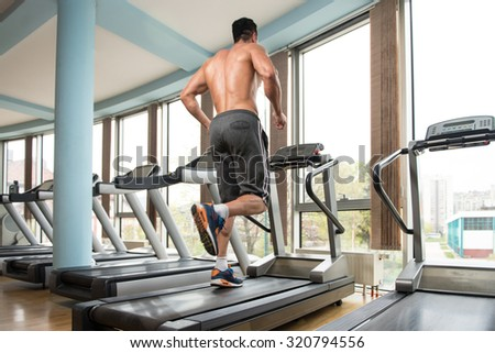 Handsome Man Running On The Treadmill In Gym - stock photo