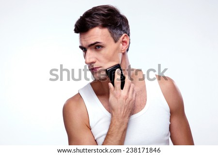 Handsome man shaving with electric razor over gray background - stock photo