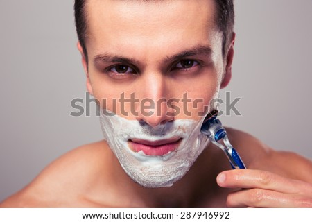 Handsome man shaving with razor over gray background - stock photo