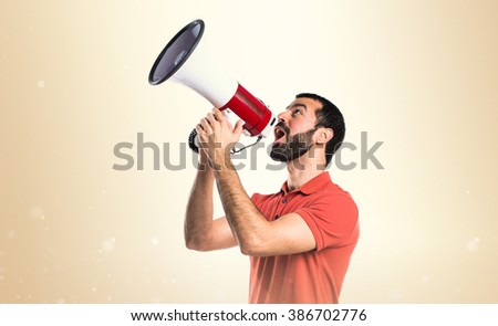 Handsome man shouting by megaphone - stock photo