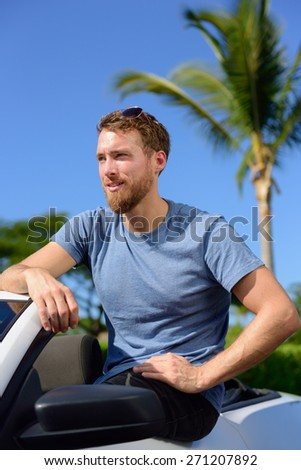 Handsome man showing off new luxury cabriolet car. Portrait of confident Caucasian young male in his 20s owner of a grey convertible car, purchase or rental. Summer road trip concept. - stock photo