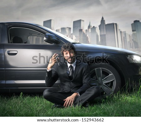handsome man showing the keys of his car sitting on the grass - stock photo