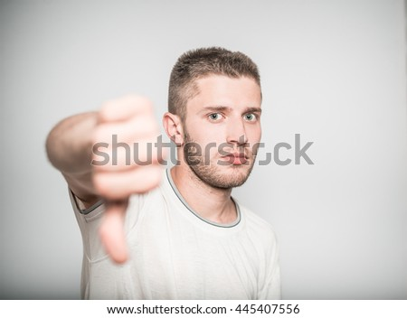 handsome man shows gesture thumbs down, isolated on a gray background - stock photo