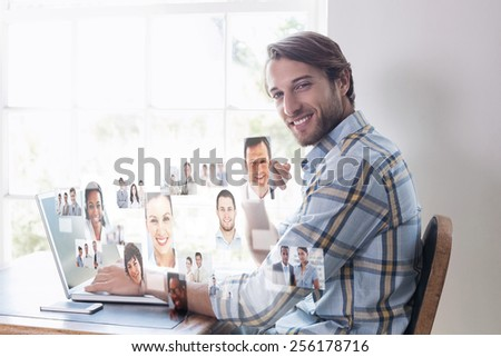 Handsome man sitting at table using laptop against business people - stock photo
