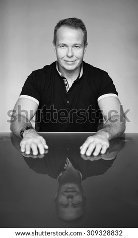Handsome man sitting at the table - stock photo