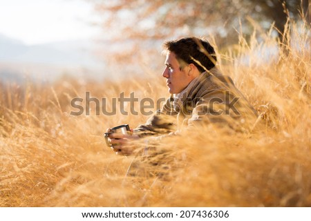 handsome man sitting in tall grass in autumn - stock photo