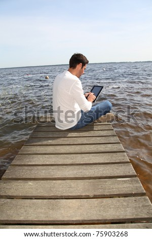 Handsome man sitting on a pontoon with touchpad - stock photo