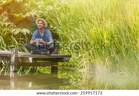 handsome man sitting on a wooden pontoon and using a digital tablet in summertime - stock photo