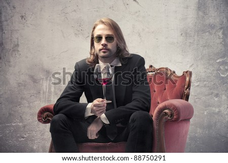 Handsome man sitting on an armchair and holding a glass of wine - stock photo