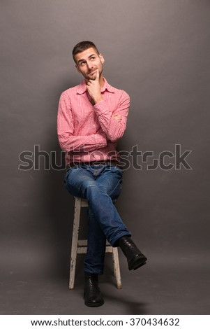 Handsome man sitting on the chair, touching his face while wearing jeans and shirt isolated on grey background. - stock photo