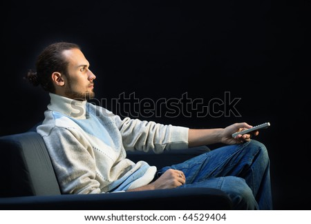 Handsome man sitting on the couch in the dark changing TV channeels with remote control - stock photo