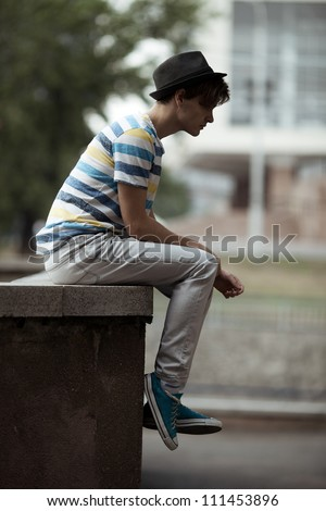 Handsome man sitting on the curb in city - stock photo