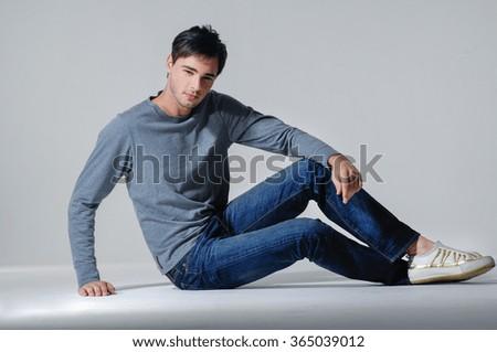 Handsome man sitting on the floor - stock photo